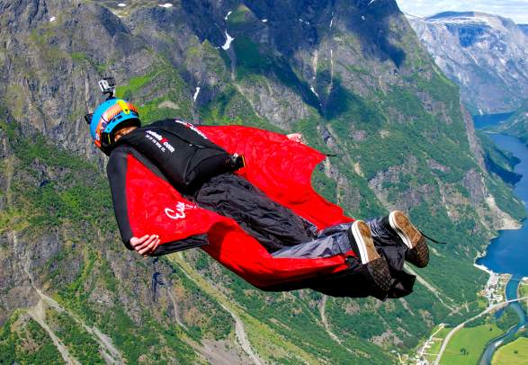 A person BASE jumping with a wingsuit in Voss in Fjord Norway