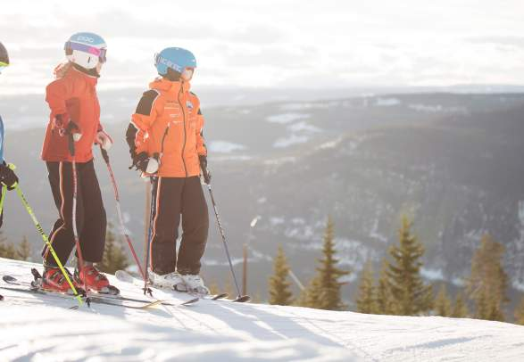 Three youngsters standing on top of a slalom slope in Hafjell, Norway
