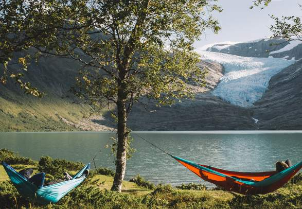 People in hammocks in front of the Svartisen glacier in Helgeland, Northern Norway