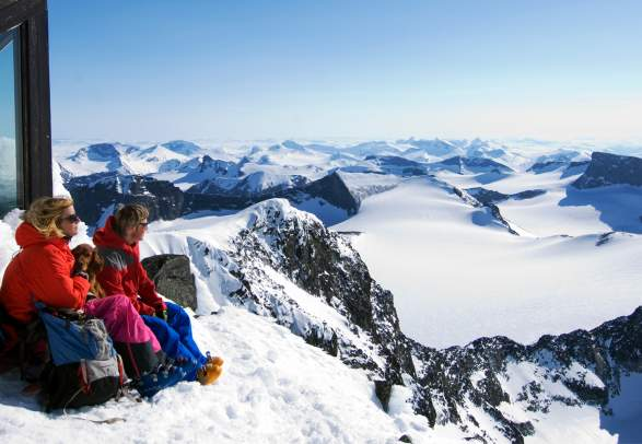 Two people admiring the view from Galdhøpiggen in Jotunheimen in winter