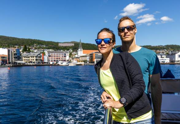 A man and a woman standing on a boat in Molde in Northwest, Fjord Norway.