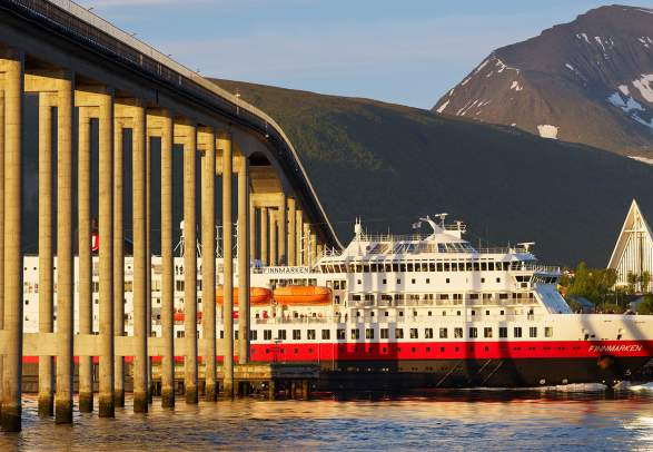 Hurtigruten sailing under a bridge in Tromsø