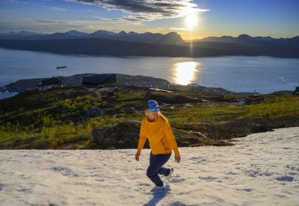 A woman is enjoying a late hike under the midnight sun in Narvik, Northern Norway