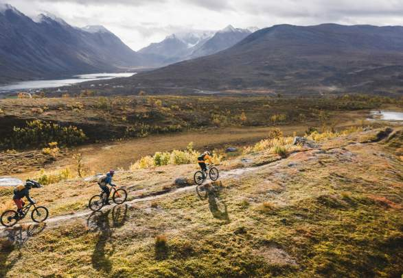 Three people mountain biking in the Lyngenfjord region in Northern Norway, in the mountains