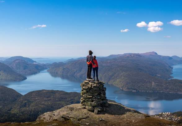 A couple on a mountain top with fjord view in Suldal in Ryfylke, Fjord Norway
