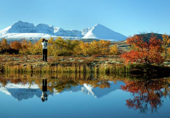 A woman taking photos of a lake and trees in autumn colours in the Rondane national park, Eastern Norway. Snowclad mountains in the background.