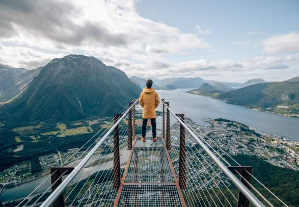 A person standing at the tip of Rampestreken viewpoint, looking out at the fjord and mountains of Åndalsnes in Northwest, Fjord Norway.