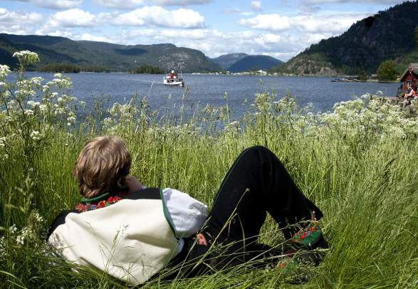 A man in the national costume Setesdalsbunad lying in the grass and watching an old steamboat on the Byglandsfjord in Setesdal, Southern Norway