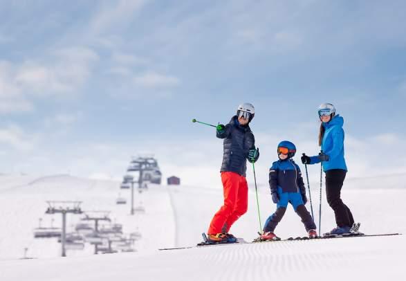 Een gezin van drie aan het skiën op de pistes van de berg Trysilfjellet in Trysil, Oost-Noorwegen.