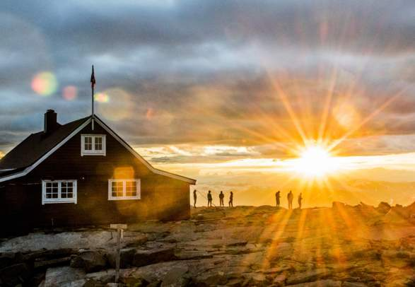 People watching the sunset at the Fannaråken cabin in Jotunheimen, Norway