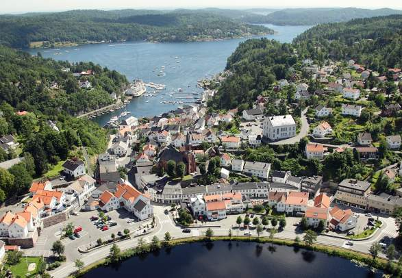 The idyllic white-painted city of Tvedestrand from the air, between the fjord and the city lake Tjenna. Southern Norway.