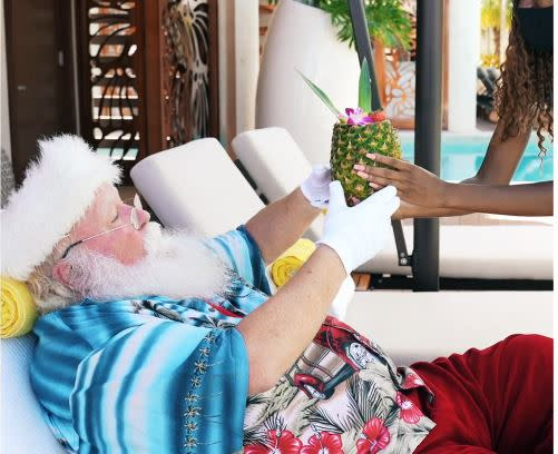 Santa Lounging at the pool being handed a tropical drink