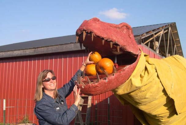 Woman with pumpkin-eating dinosaur at Great Country Farms
