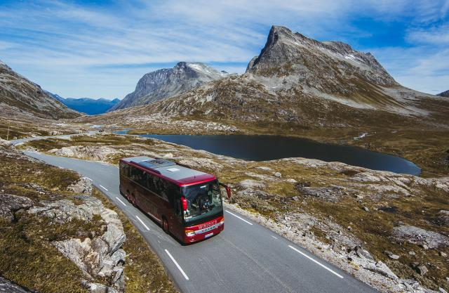 A bus driving next to a lake on a sunny day in Northwest