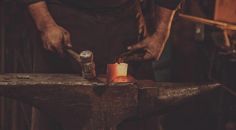 Close up of blacksmith hands forging hook at Cloverdale Forge