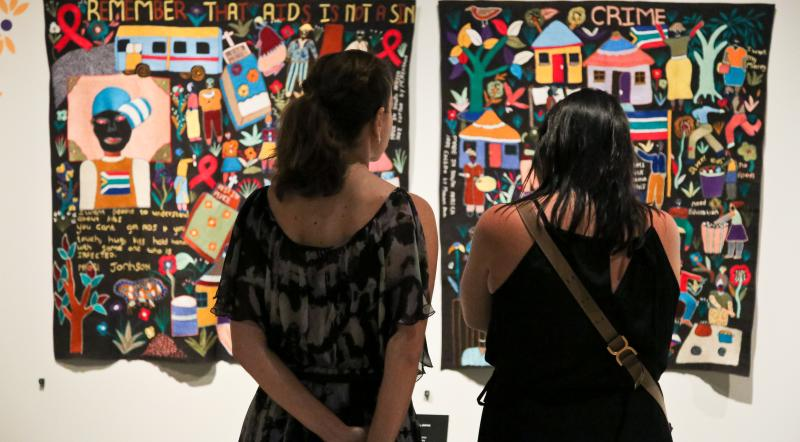 Two visitors in front of Mapula Embroidery Project Quilt from South Africa — photo by Leif Norman