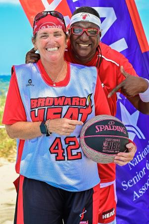 Two basketball players from the National Senior Games posing with a basketball in front of the event's flag
