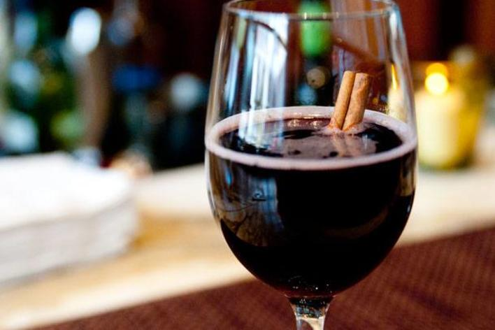 A glass of red wine with cinnamon sticks inside