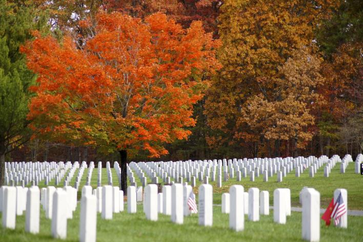 A cemetery with matching white headstones in lines, there are trees with fall foliage in the background