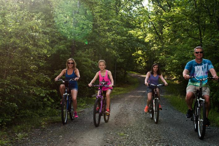 family biking on a path in the forest