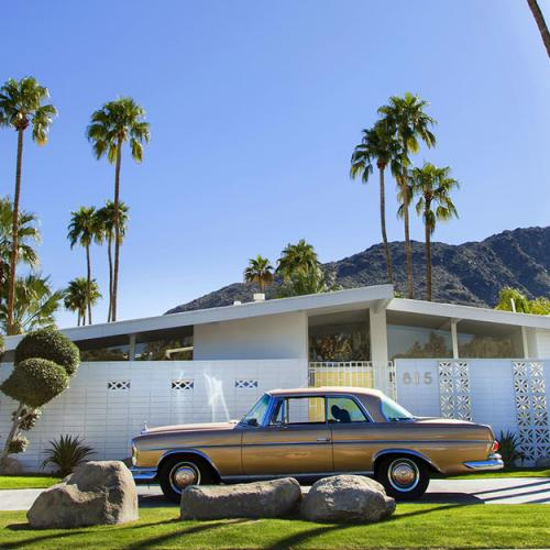 A classic car parked in front of a midcentury modern home