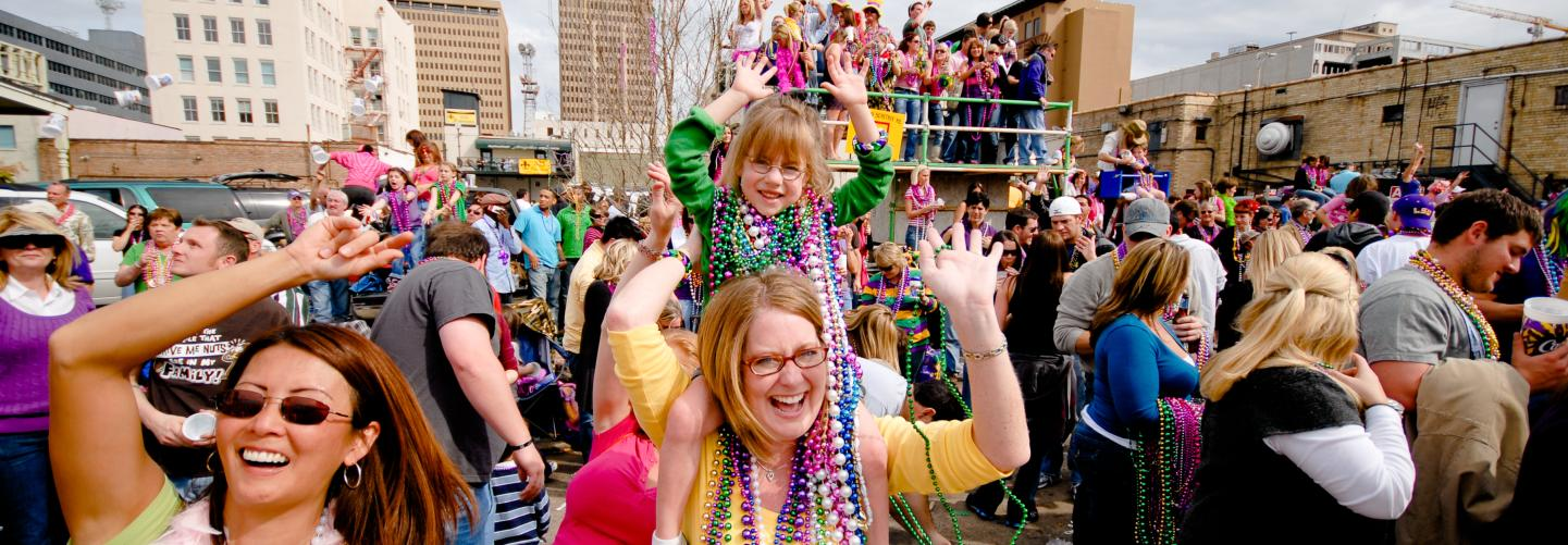 Kids and families sporting lots of beads and having fun during Mardi Gras events