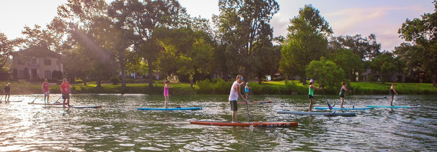 People stand-up paddle-boarding down peaceful river