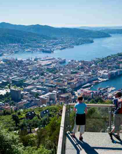 A man and a woman enjoing the view at Mount Fløyen in Bergen