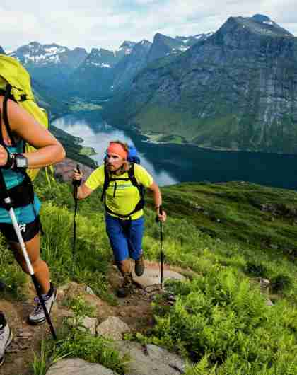 Two people hiking in the mountain landscape by the Hjørundfjord