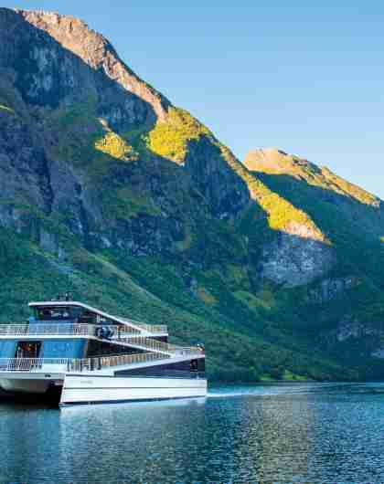 The hybrid electric vessel Vision of the Fjords cruising the Aurlandsfjorden fjord surrounded by mountains
