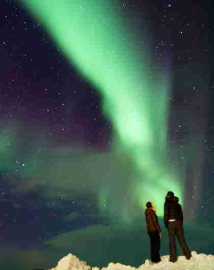 A couple enjoying the beautiful northern lights in Finnmark, Northern Norway