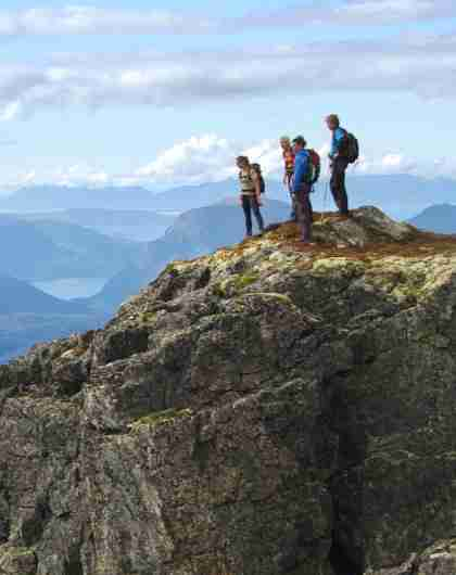 A group of people admire the view from Romsdalseggen in Norway
