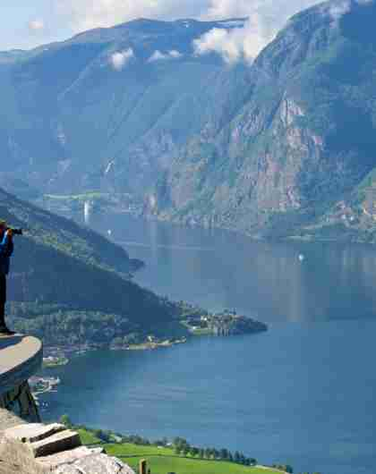 A man standing at a viewpoint taking pictures of the Aurlandsfjord