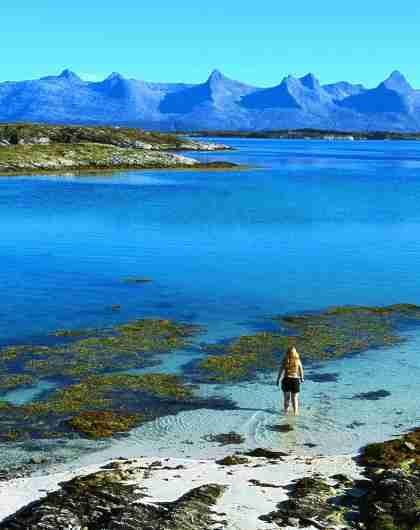 A woman standing in the sea on Herøy island with a view of The seven sisters mountain range on Helgelandskysten, Norway