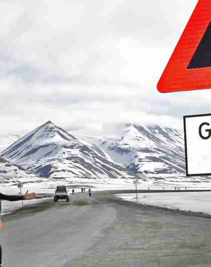 A marathon runner passing a polar bear warning sign in Spitsbergen in Svalbard