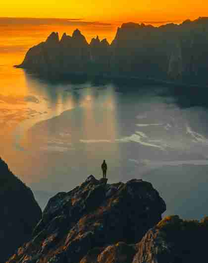 A man standing on the tip of a mountain in the midnight sun at Senja