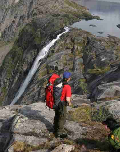 A person and two dogs looking at Litlverivassfossen in Rago national park