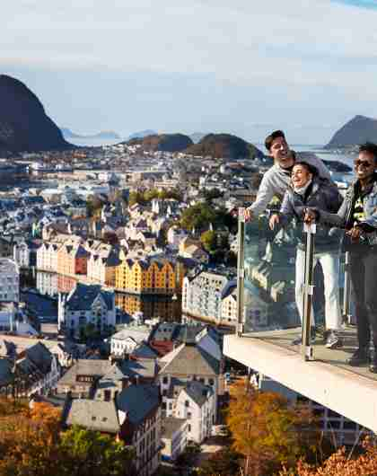 Three people standing on a viewing platform at Mount Aksla in Ålesund, Fjord Norway