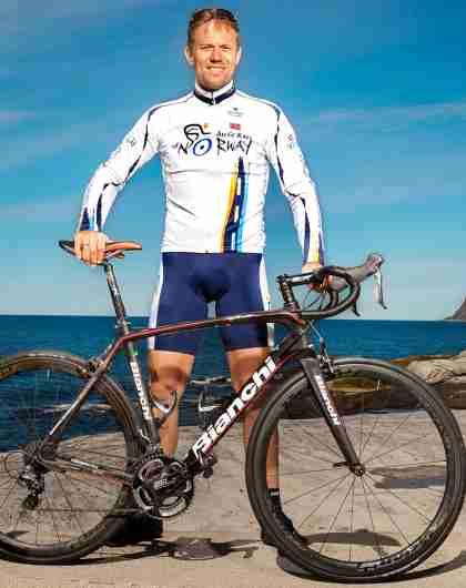 Thor Hushovd står bak sykkelen sin med sjøen i ryggen