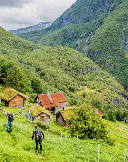 Two people walking towards the mountain farm Avdalen Gard in the Utladalen valley, Fjord Norway
