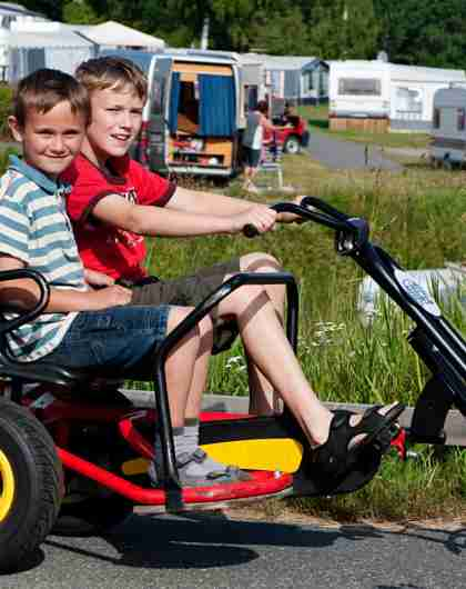 Two boys in a toy car at Sørlandet feriesenter camping ground