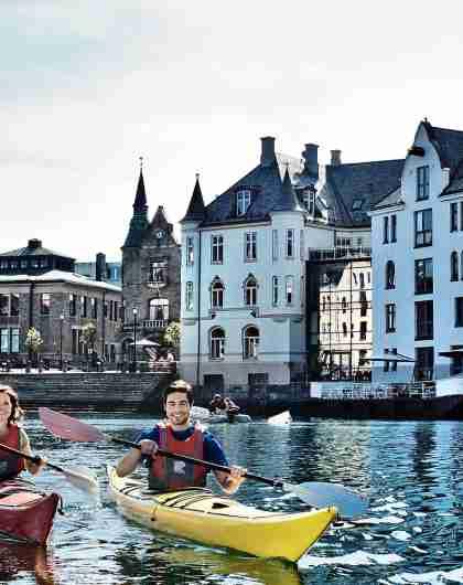 To personer padler kajakk midt i Ålesund på Vestlandet