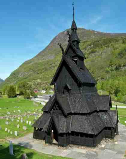 Borgund stavkirke omringet av frodig landskap med gravsteiner og trær