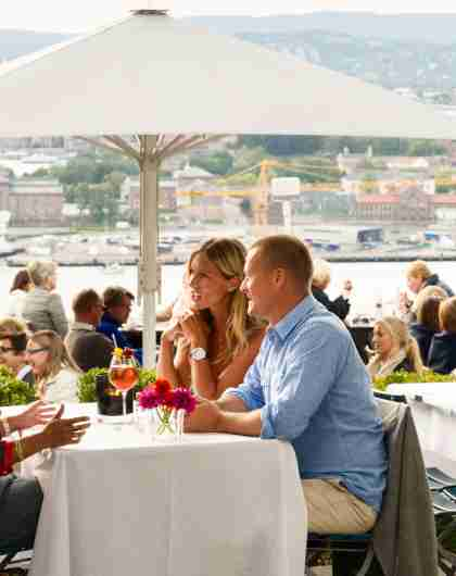 The terrace of the Ekebergrestauranten filled with people, overlooking the Oslofjord, Eastern Norway
