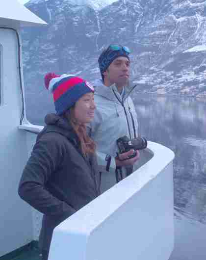 Two people standing on a boat enjoying the view of the Nærøyfjord in winter