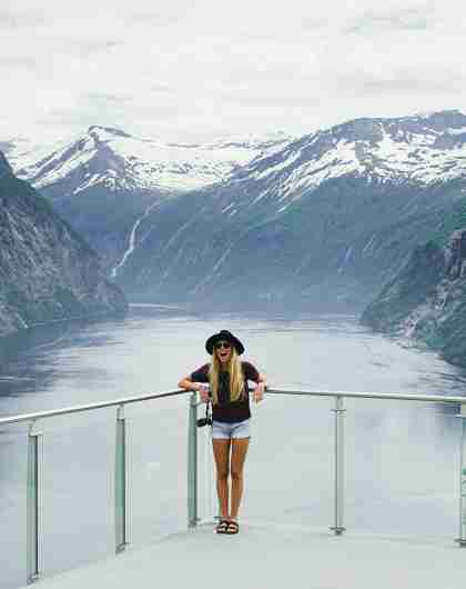A woman standing at Ljøen viewpoint in Hellesylt