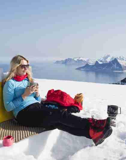 En dame nyter nistepause på toppen av Ryten i Lofoten, Nord-Norge