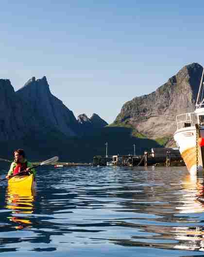 Two people kayaking next to a fishing boat in Reinefjorden in Lofoten