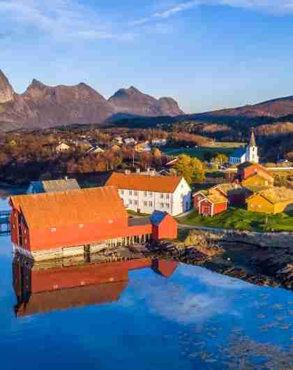 Det gamle handelsstedet på Kjerringøy i Bodø i Nord-Norge med fjell i bakgrunnen.