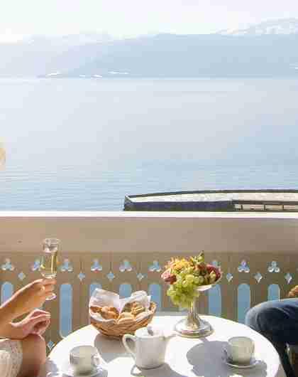 A couple having breakfast at the balcony at the Historic Hotel Kviknes in Balestrand